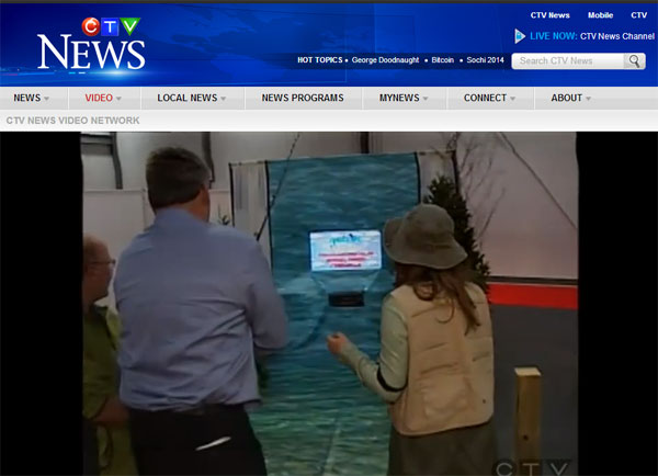 """John Fraser, Ottawa South M.P.P. tackles the """"heart stopping"""" fishing action provided by the  Go Fish In Ontario / Canadian Sportfishing Interactive Fishing Simulator at the 2014 Ottawa Sportsmen Show."""