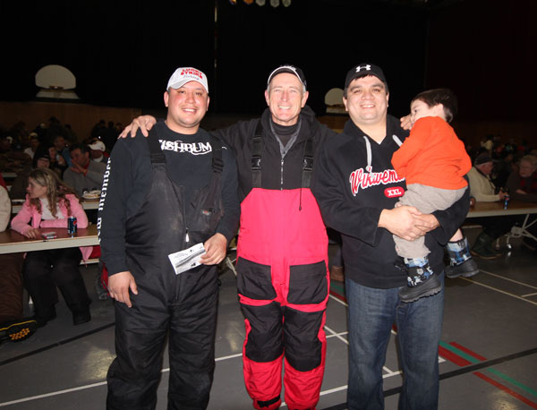 Luc Wassegijig, the Ice Fishing Derby founder and manager posses with myself and Chief Duke Peltier and his son.