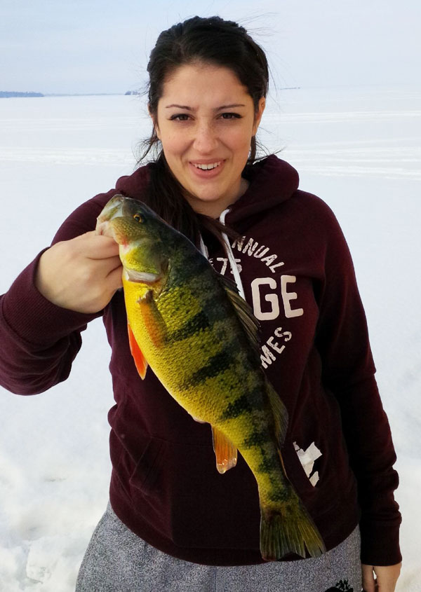 Natale Felekides smiles as she holds up a trophy jumbo perch she caught while fishing with her dad George and her sister on Lake Simcoe, ON.