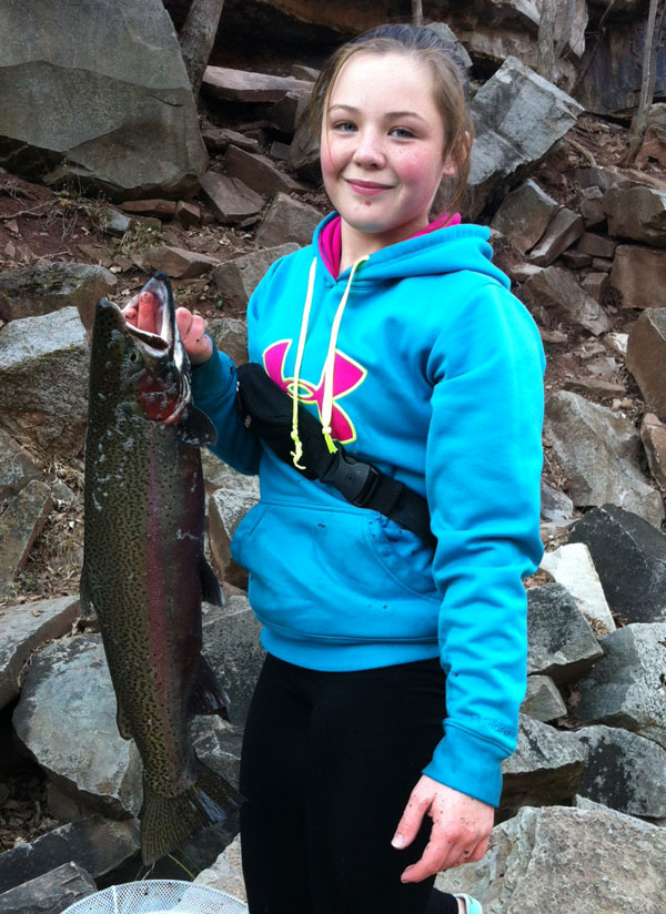 Mikayla smiles as she hold up a trophy male rainbow that sports it bright spawning colors.