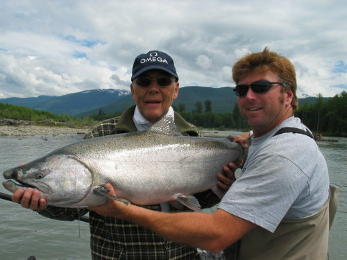 Pro angling guide Tracey Hittel of Kitimat Lodge assisting his guest Frank Aldo from Switzerland to pose one of his BIG Kitimat River Chinook (King) Salmon. He landed seven Chinook on this day in July. PRIME TIME Chinook on Kitimat and Skeena Rivers mid June to August 7.